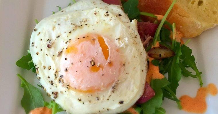 Sunny Side up Egg, over Arugula, Red Pepper Cream, Sautéed Potatoes and Prosciutto