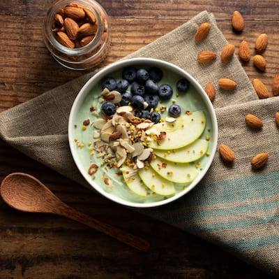 Green Apple Yogurt Bowl topped with blueberries, sliced green apple, and shaved almonds served in a white bowl. The bowl is sitting on a golden burlap and teal napkin with almonds sprinkled on the table