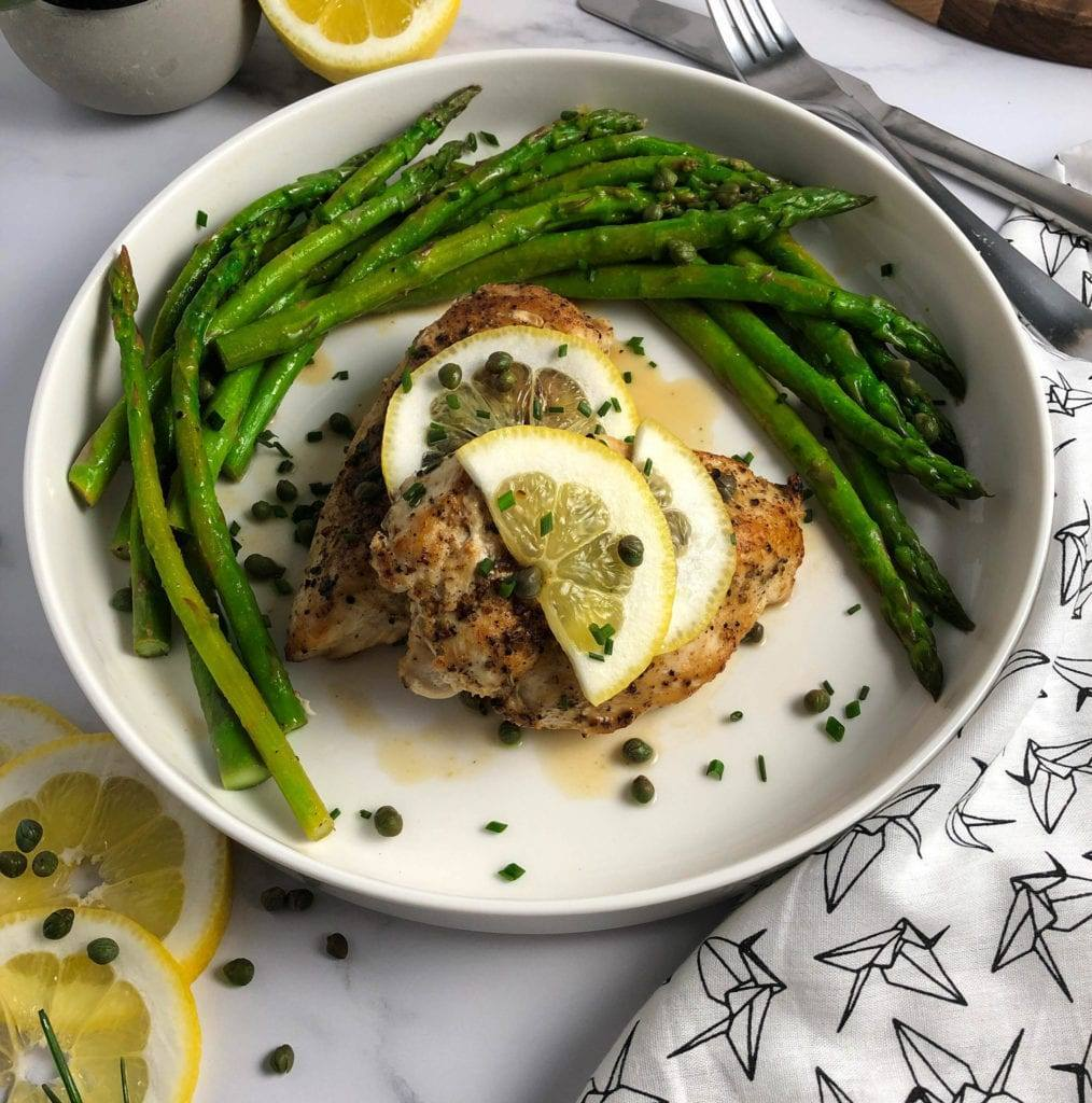 Chicken and Asparagus with Lemon Caper Sauce, Sliced lemons with chives and capers on the table
