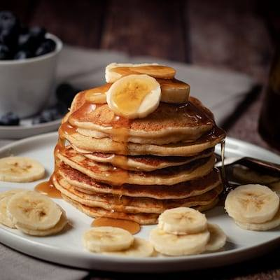 Banana Pancakes toped with bananas and syrup, on a white plate with a bowl of blueberries in the background