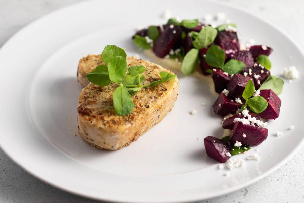Swordfish Roasted Beet Parsnip Puree served on a white plate, sprinkled with micro greens and goat cheese