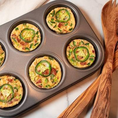 Chicken Sausage Egg Bits in a muffin tin with wooden spoons