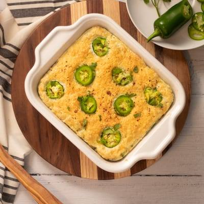 Jalapeno and Egg White Casserole placed on top pf a stripped wooded cutting board with a white plate of sliced jalapeños
