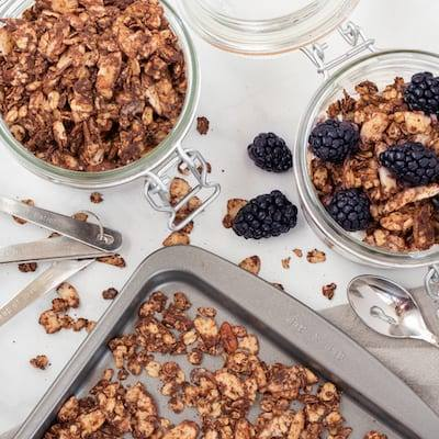 Savory Chocolate Granola on a metal baking sheet, and in two mason jars.