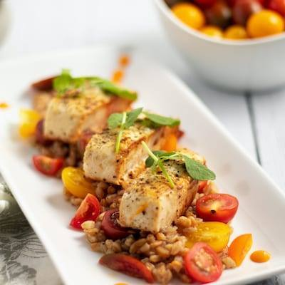 Mahi Mahi on a Bed of Farro and Heirloom Tomatoes on a white plate with a bowl of tomatoes in the background