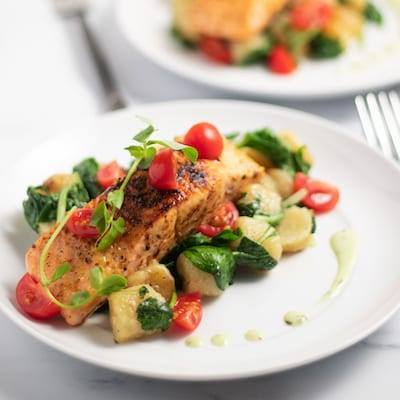 Salmon with Cauliflower Gnocchi and tomatoes and spinach on a white plate with metal forks on each side