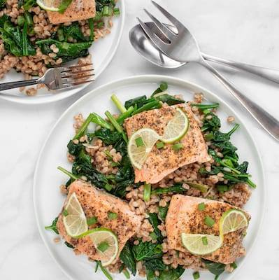 Salmon with Farro and Onions and Spinach served on a with plate with a lime twist and large metal serving spoon and fork