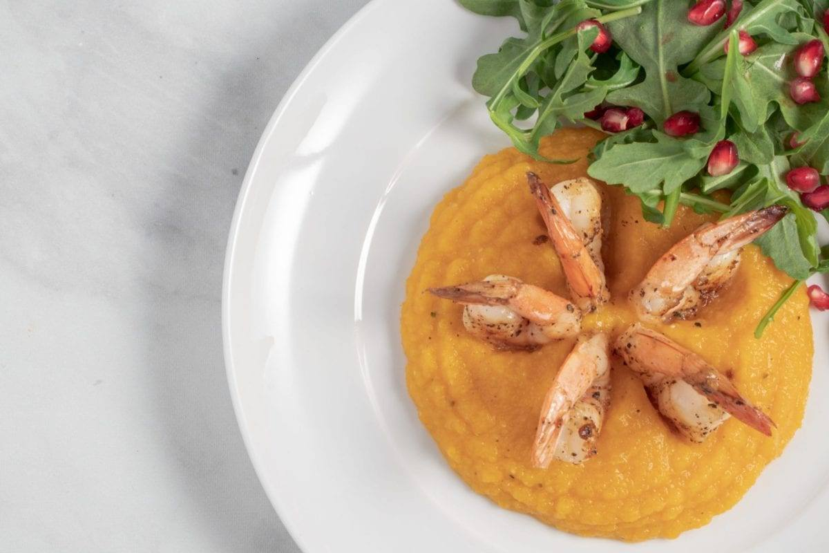 Roasted Butternut Squash Puree with Shrimp in a white bowl with a side arugula salad