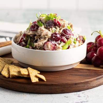 Chicken and Grape Waldorf salad Served on a stripped wooden cutting board with crackers fanned out around it, and grapes sitting on the cutting board wit a cream and grey stripped napkin and wooden spoon.