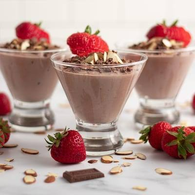 Chocolate Almond Yogurt topped with Strawberries chocolate shavings and served in three martini glasses with almonds, chocolate, and strawberries sprinkled around the table.