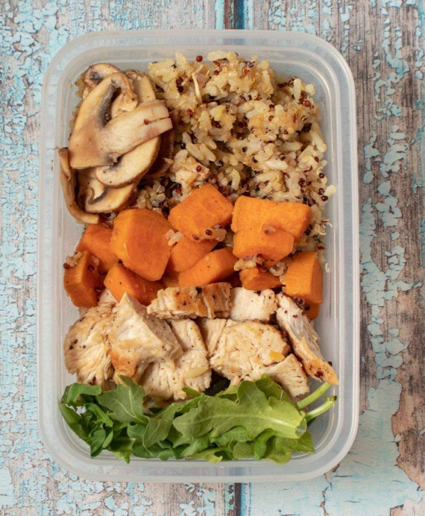 Dirty Rice and Sweet Potatoes with Chicken Served in a Plastic Container