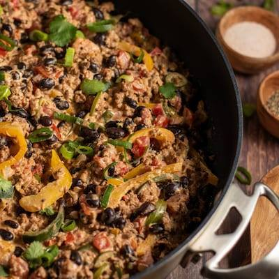 Keto Mexican One Pot Meal in a large black pan with a beige napkin and wooden serving spoon