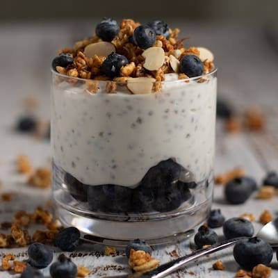 Blueberry Chia Seed Parfait in a glass with granola and blueberries all around it.