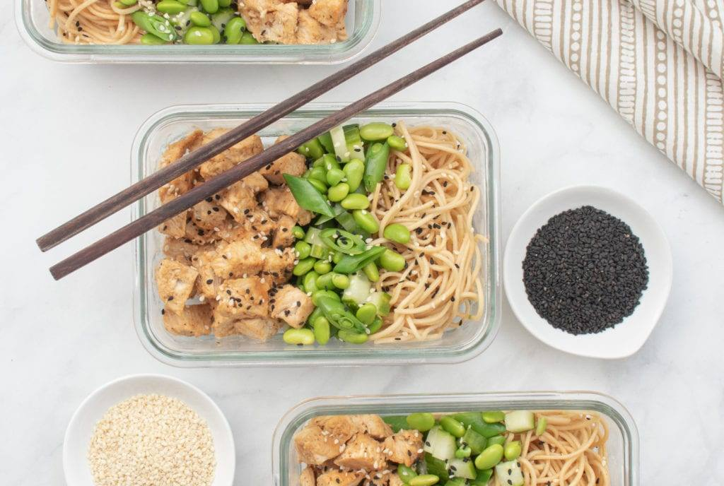 Sesame Chicken Noodle Bowl with Edamame and English Cucumber Served in Glass Reusable Containers with chop sticks and bowls of black and white sesame seeds