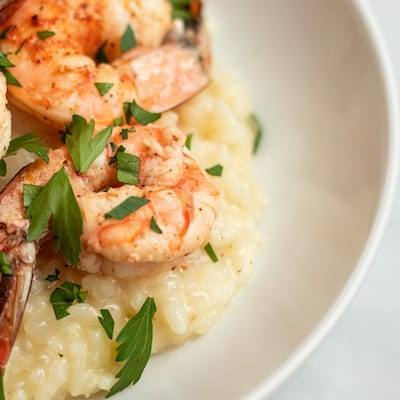 Lemon Risotto and Shrimp Served in a white bowl on a marble counter
