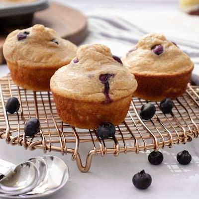 Blueberry Pancake Protein Muffins sitting on a gold drying rack with heart shaped measuring spoons sitting on the counter next to them.