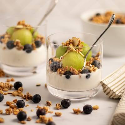 Honeydew parfait. Yogurt topped with blueberries and melon balled honeydew and sprinkled with granola served in a glass with a small spoon.