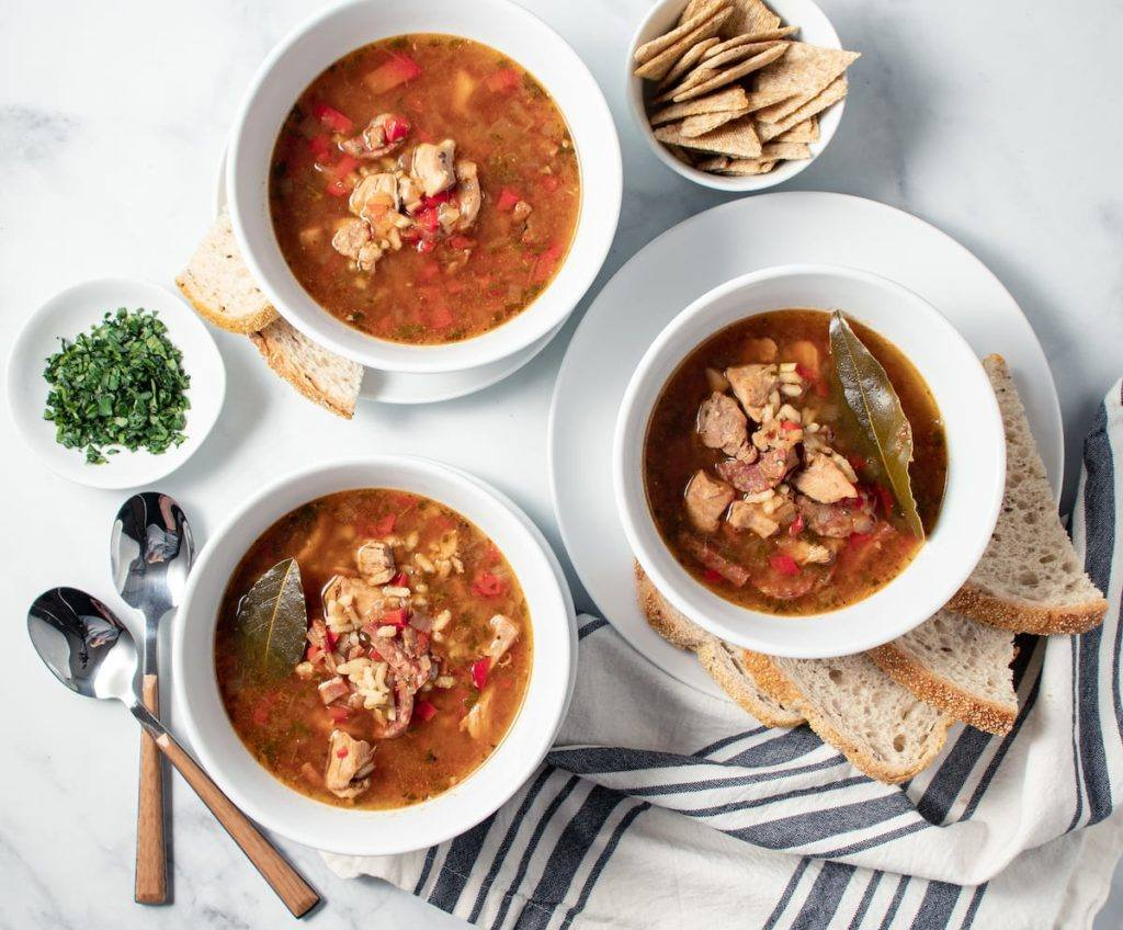 Puerto Rican Asopao Chicken and Rice Stew served in a white bowl with crackers and bread Meal Prep Meal Planning Counting Macros