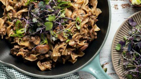 One Pot Beef Stroganoff Recipe, Noodles and beef cooked in a mushroom soup. Cooked in a light blue cast iron pan. Great for meal prep, counting macros, freezer friendly