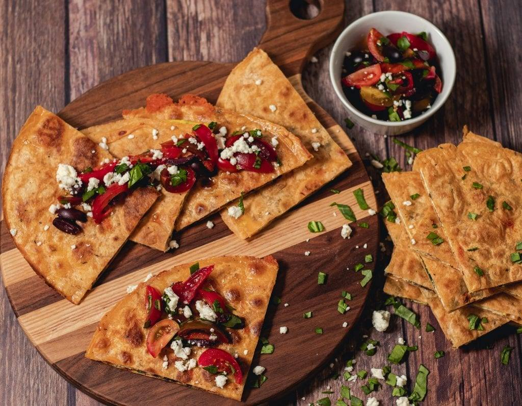 Greek Breakfast Quesadilla w/Spinach & Mushroom Meal Planning Meal Prep Counting Macros on a cutting board sprinkled with feta, tomatoes, and olives.