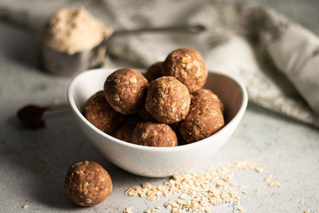 Vanilla and Cinnamon Protein Balls in a white bowl with split oatmeal around it. Meal Planning Meal Prep Counting Macros