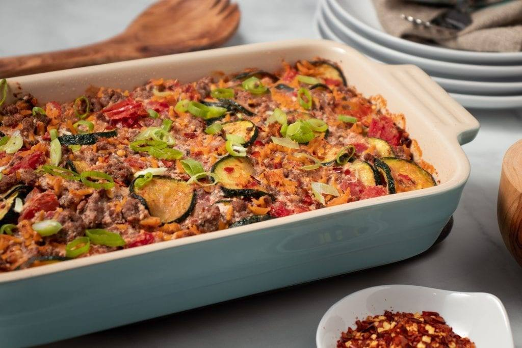 Zucchini & Ground Beef Orzo Casserole, In a cream and blue casserole dish, with red pepper flake. Great for meal prep, freezer friendly, and can be easily adjusted to fit your goals if your counting macros, add this recipe to your meal plan today.