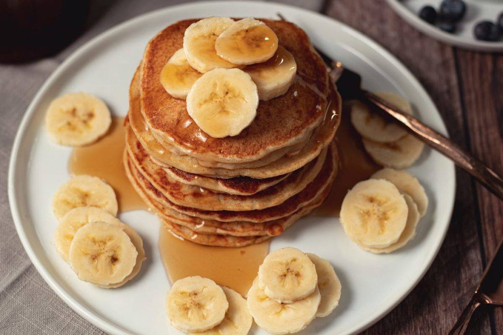 Easy, Healthy High Protein Banana Pancakes, served on a white plate with bananas on top and drizzled with syrup
