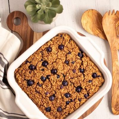 Blueberry Quinoa Protein Bars in a hite casserole dish next to wooden serving spoons, and cream napkin with grey strips and a plant