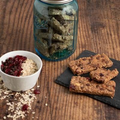 Chewy Cranberry Granola Bars on a black cutting board next to a green glass gar filled with granola bars