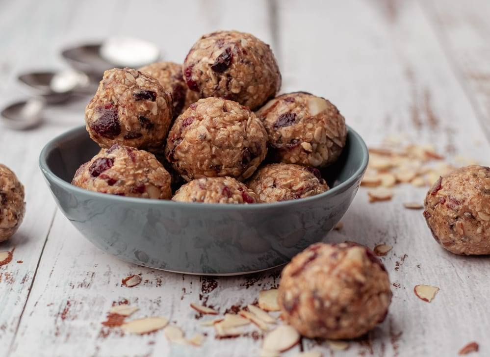 Cranberry Oatmeal Peanut Butter Bliss Balls in a blue bowl Meal Prep Meal planning Counting Macros Macro Friendly