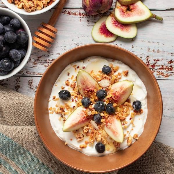 Fig Yogurt Parfait severs in a brown bowl with blueberries on top with granola and honey.