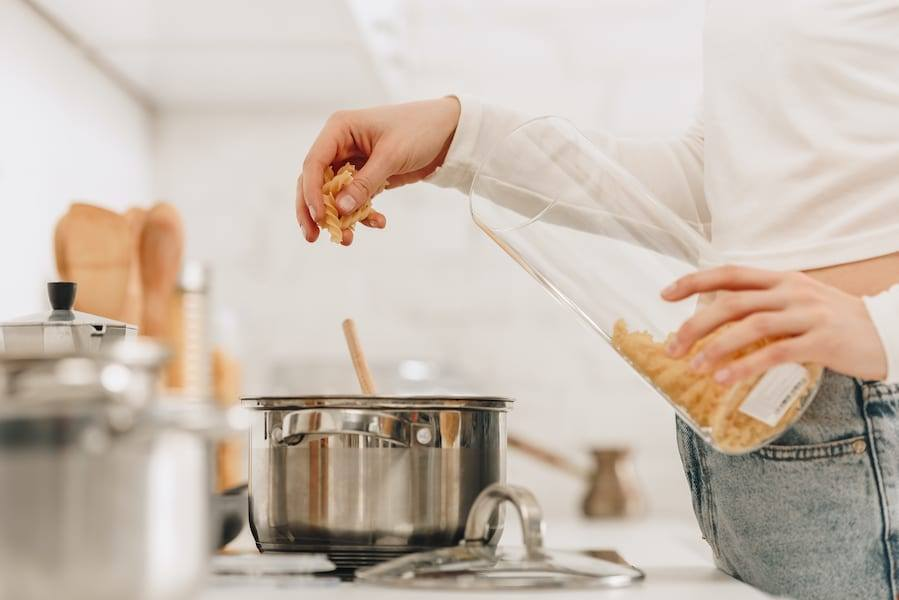 Women wear white shirt and jeans Reheating Meal Prepped Food on a stove in a pot