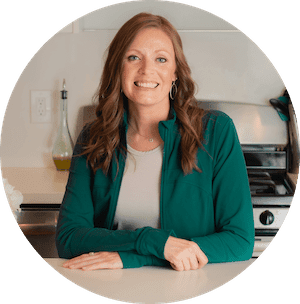 About Me Jenn Lamb A Dash of Macros Profile Photo A Women sitting and her kitchen counter wearing a green sweater over a grey shirt Healthy Recipes