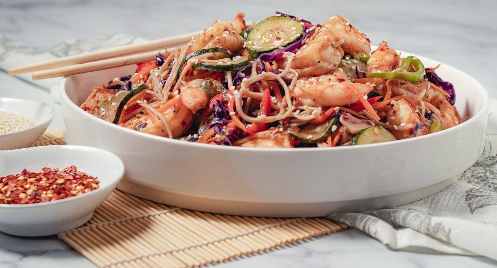 Simple Spicy Shrimp and Soba Noodle Stir Fry Recipe, a healthy meal prep recipe, that is great if your counting macros, add this recipe to your meal plan today. Stir fry on a large white plate with chop sticks, and red pepper flake and sesame seeds on the side.