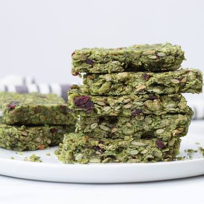 Pumpkin Seed Granola Bars stacked on top of each other, on a white plate with a white and grey stripped napkin in the background.