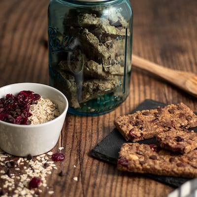 Chewy Cranberry Granola Bars in a blue glass jar sitting on a wood table, next to a bowl of Cranberries and oats and more granola bars on a black board.
