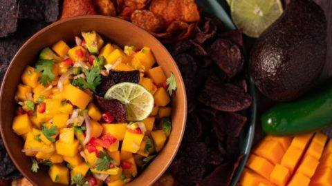 Easy 5 Minute Mango Salsa served in a brown bowl surrounded by multi colored chips
